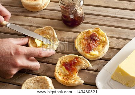 Pair of hands using knife to spread strawberry marmalade on toasted english muffins next to jelly jar and yellow stick of butter