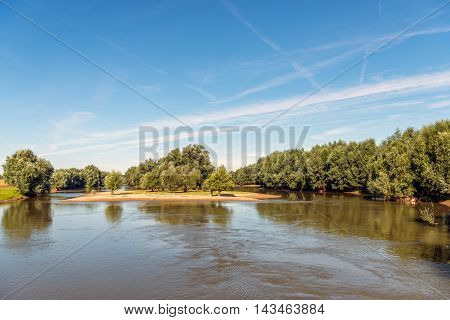 Small idyllic island in a Dutch nature reserve in the summer season. It's a windless day and the contrails remain long visible in the blue sky.