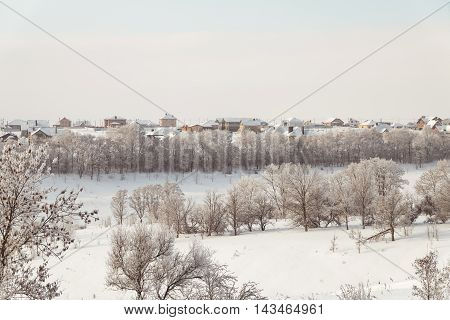 Winter. January snow-covered landscape of the ravine on a background of low-rise housing