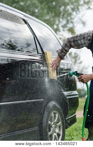 man washes his car on a background of green garden