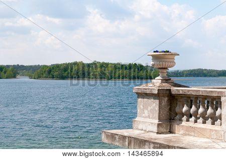 Bowl with flowers with Galve lake in background Uzutrakio palace Trakai Lithuania