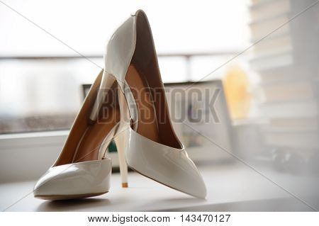 White lacquer women's shoes with high thin heels. Shoes for bride in waiting. Women's elegant shoes.