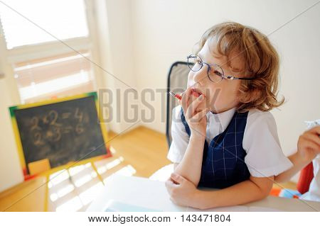 Cute little schoolboy in glasses has fallen into a reverie. The boy leaned his head on his hand and looking somewhere to the side. This elementary school student. Back to school.