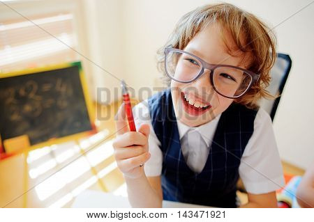 Funny little schoolboy in glasses sits at a school desk. It is a disciple of an elementary school. In a hand at boy ball pen. On a school desk copybooks lay. Near to a school desk a small blackboard.