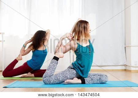 Two beautiful women doing kapotasana and meditate with eyes closed, side view portrait