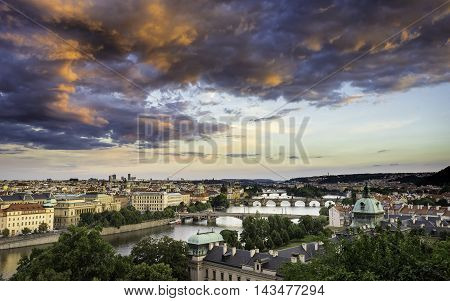 Skyline of Prague bridges on Vltava river during afternoon. Storm clouds with red color. old Town Prague Europe.