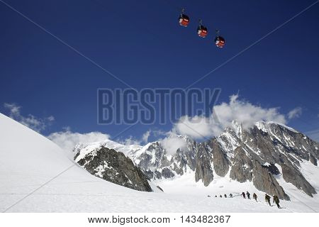 Mont Blanc and the Mont Blanc Massif with Cable Cars in the Blue Sky and Alpine Mountaineers on the Glacier. Aosta Valley Italy
