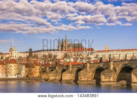 Charles Bridge under a cloudy sky - Cityscape with St. Vitus Cathedral in background and the Charles Bridge in foreground, under a beautiful sky. Picture captured in Prague, Czech Republic