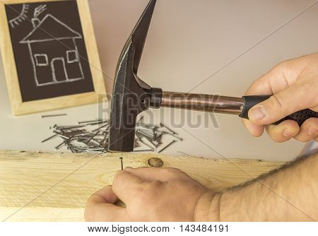 Man's hand hammering nail in wood - Image with a builder's hand hammering a small nail in a wooden board and in the background a chalkboard with a funny drawing of a house.