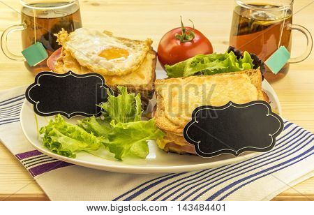 Sandwiches and tea cups for a pair - Plate with sandwiches, fried egg, tomato and green salad on wooden table. Each sandwich has a blank paper tag for short messages.