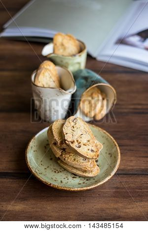 Traditional homemade italian cantucci or cantuccini cookies with almond nuts on a small green plate and in the small cups on a wooden rustic table, selective focus