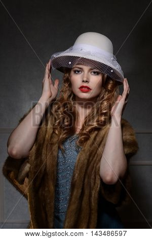 portrait of 1940s style fashion woman wearing white hat