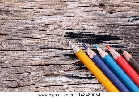 Colored pencils or Crayons on old wooden floor concepts about education.