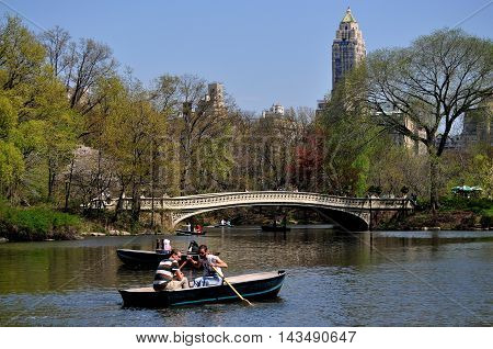 New York City - April 24 2013: People in rowboats on the Central Park boating lake near the graceful 1864 Bow Bridge on a warm Spring afternoon