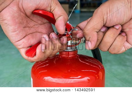Hand pulling pin of fire extinguisher, protection, illustration