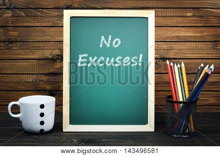 No Excuses text on school board and group of pencils