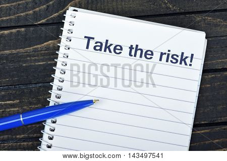 Take the risk text on notepad and blue pen