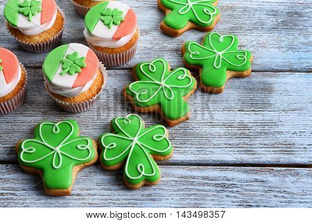 Decorative cookies and cupcakes on wooden background. Saint Patrics Day concept