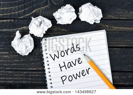 Words have power text on notepad and crippled paper