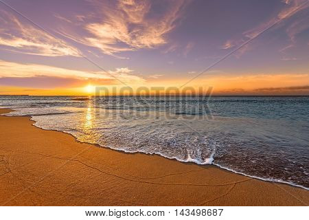 Colorful ocean beach sunrise. Golden sands and blue sky