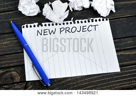 New project text on notepad and crippled paper