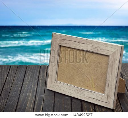 Photo frame on wooden table and sea