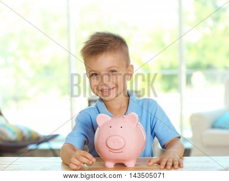 Savings concept. Little boy sitting at table with piggy bank