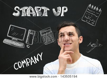 Attractive young man on blackboard background. Business trainer concept.