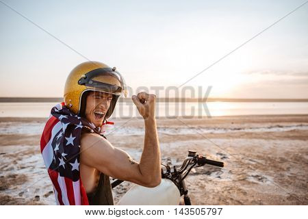 Smiling brutal man in golden helmet and american flag cape sitting on his motocycle showing biceps outdoors