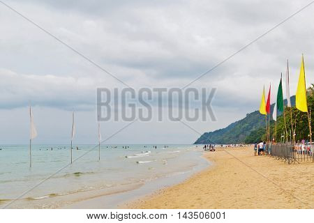 KOH CHANG, THAILAND- APRIL 12, 2015: Thais and tourists walking and resting on the White sand beach of Chang island before sunset. Koh Chang is a famous tourist destination in Thailand