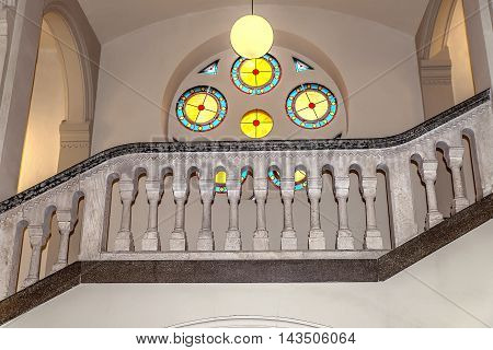 A fragment of the marble staircase with balusters and railing against the backdrop of stained glass