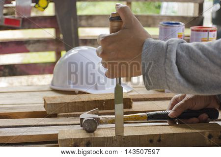Carpenter using  chisel and hammer in his hand with plank.Close up and stillife.0001