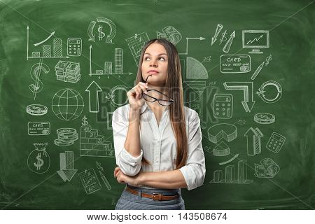 Cropped portrait of a young businesswoman with glasses thoughtfully looking upwards on the background of a chalkboard with business doodles. School and education. Learning and teaching.