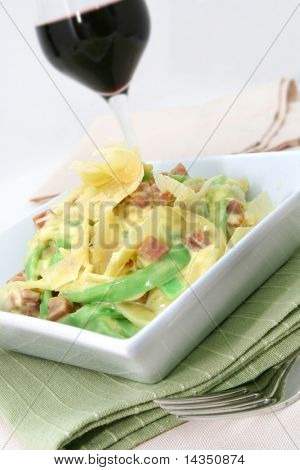 Fettucine carbonara in a square white bowl, with glass of red wine.  Ribbon pasta with a creamy bacon sauce, and fresh-shaved parmesan cheese.