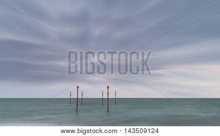 Stunning Vibrant Conceptual Image Of Posts In Sea Standing Sentinel Against The Weatherand Tide