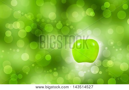 Green apple with light aura on green bokeh background