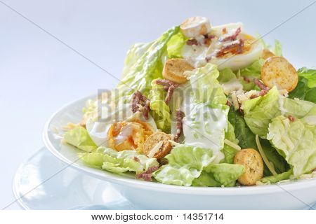 Caesar salad in white bowl, in natural window light.