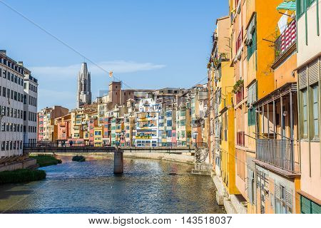 Girona Spain - July 30 2016. Onyar river crossing the downtown of Girona with bell tower of Basilica of Sant Feliu in background. Gerona Costa Brava Catalonia Spain.