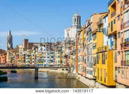 Onyar river crossing the downtown of Girona with bell tower of Basilica of Sant Feliu and Santa Maria cathedral in background. Gerona Costa Brava Catalonia Spain.