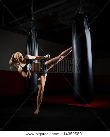 Training of kickboxer woman at gym