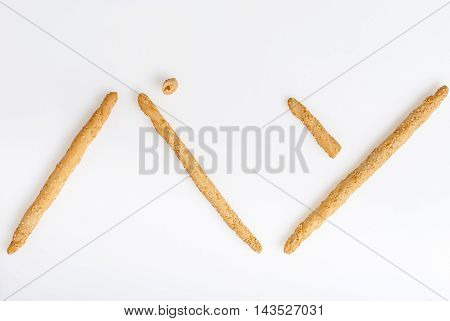 Excellent and natural breadsticks with sesame seeds with them clearly visible on the surface Arranged so that they form the Japanese Kanji ideogram for bread and isolated on white background