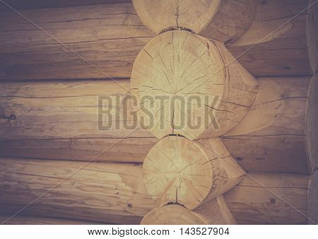 Log house corner details - Architectural image with the exterior corner and part of the wall of a log house, traditional built from round wooden beams.
