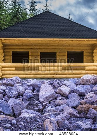 Wooden cabin and stone - Rustic wooden cabin made from beams with a shingle roof, having in front of it a stone slope