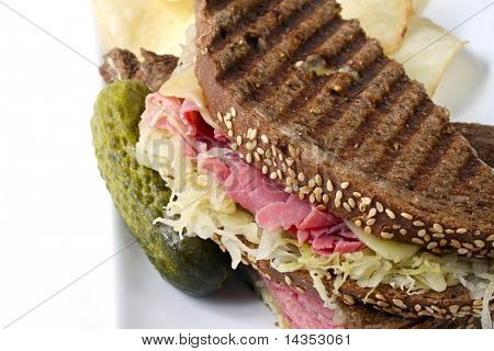 Reuben sandwich on rye bread, with corned beef, sauerkraut and Swiss cheese.  Served with a pickle and potato chips on the side. poster
