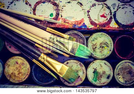 Artist paint brushes on background of gouache paint jars. Brush paint artistic. Tools for creative work. Watercolor paintbox. Back to school. Paintings Art Concept. Top view.