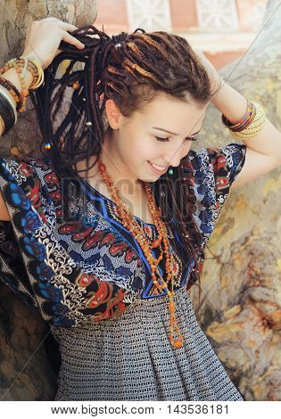 Young smiling woman portrait with dreadlocks dressed in boho style ornamental dress posing outdoor