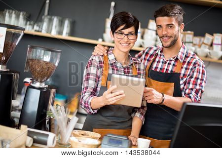 Satisfied and smile owners look on tablet orders coffee shop