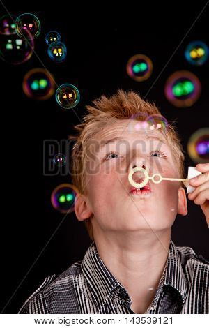 Teenage Boy Having Fun Blowing Soap Bubbles