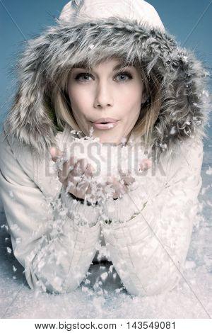 Beautiful winter woman blowing snow
