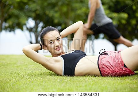 young asian woman doing sit-ups on grass in city park. poster